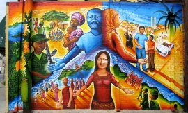 """The Global Refugee Mural"" tells the stories of three local refugees, who worked with Joel on the design. Joel was inspired to do this project after working with refugees at a refugee resettlement center run by the International Rescue Committee (IRC), who he partnered with for this project. The mural deals with the human rights abuses in each of the three refugees' homelands as well as celebrating the culture and traditions there. Funded by the Montgomery County Council on the Arts."