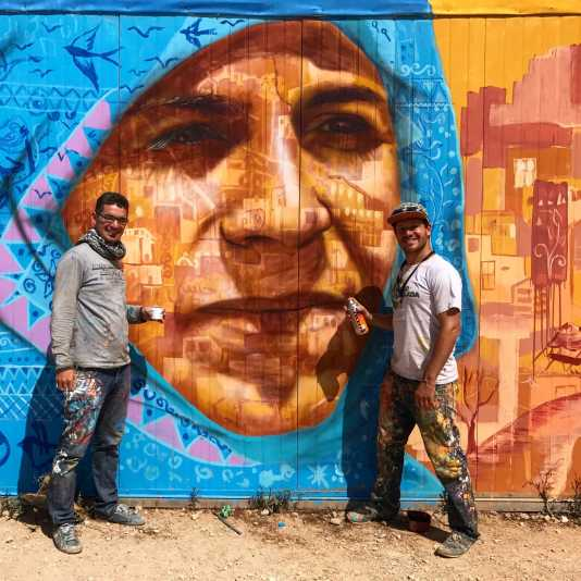Za'atari Syrian Refugee Camp, Jordan, 2017: Joel working with Syrian artist Mohammed Jokhadar on this portrait of a local woman