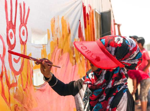 Noor works on a mural in her community in Azraq Camp