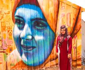 Azraq Syrian Refugee Camp, Jordan 2017: Dareen, a participant in our Azraq Camp project, poses in front of a portrait of her.