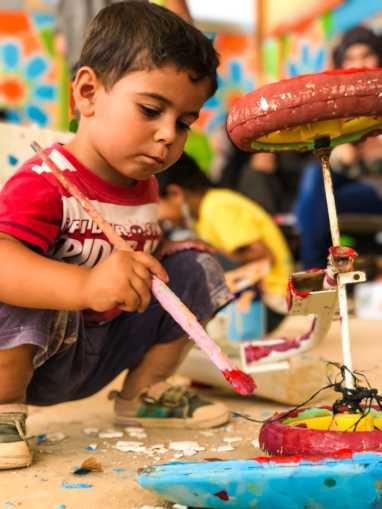 A boy works on turning trash into art!