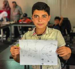 Mohammed, a 14-year-old resident of Za'atari Camp, shows his drawing depicting hope for the future after the horrors of war.