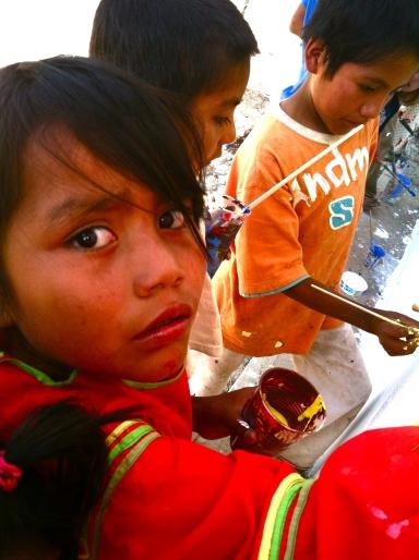 Huichol children work on a mural in their village.