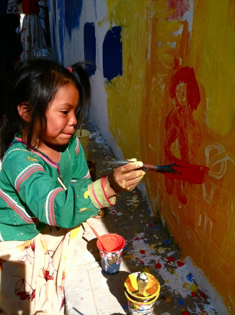 A Huichol girl works on a mural in her village.