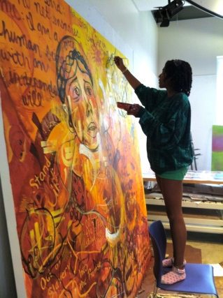 A participant adds her poetry to the mural.