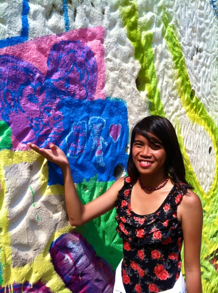 A Filipino player finishes her section of a mural in Vidigal