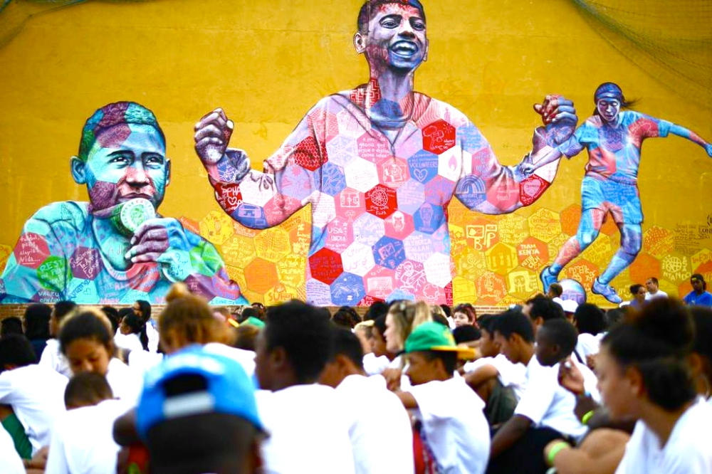 The players gather on the pitch in front of the completed mural. Photo provided by Street Child World Cup.