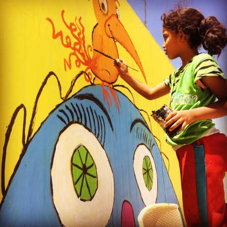 A Syrian girl painting a mural in Za'atari refugee camp