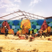 Working on a new piece right outside of the Za'atari Syrian refugee camp with boys who smuggle goods into the camp. There is little legal trade in the camp other than essentials, so these guys risk frequent beatings by the cops to make money on the huge black market. In our mural the kids envision the building of a new sense of community, as the old one has been lost.