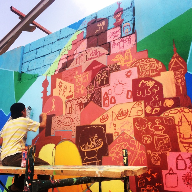 Syrian refugee kids are creating their own mural-neighborhood to reflect the growing realization that they may be displaced for a long time and must build new communities.