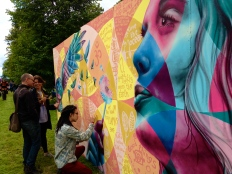 Festival-goers work on the mural at Greenbelt in the UK.