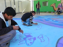 Syrian youths work on a 3D mural