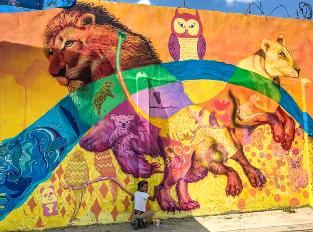 A girl puts her creativity in this animal section of the mural