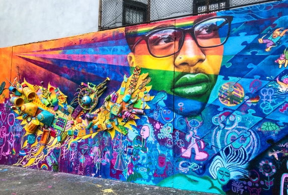 """East Village, New York City, 2018: 2 groups of teenagers, one who have struggled with bullying due to their LGBTQ identities, and another with autism and other challenges, joined forces on this mural. It includes the """"Birdstrument,"""" a sculptural element made from repurposed trash, which is also a percussive instrument. Joel co-led the project with Max Frieder. Partners: Paul Hastings Law Firm, Harvey Milk School and Manhattan School of Career Development."""