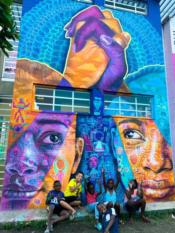 Cali, Colombia 2020: Joel collaborated with local youth and Cali artist Teca to create this mural of unity in the face of violent divisions and xenophobia in the community of Aguablanca. Partners: Artolution, Fundación Pintuco, Centro Cultural Colombo Americano.